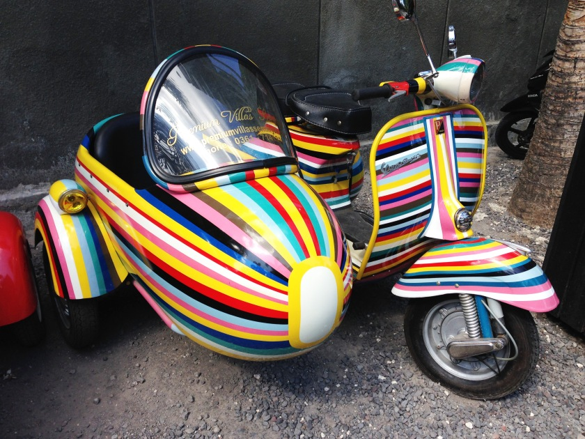 A candy-striped vintage Vespa with matching sidecar